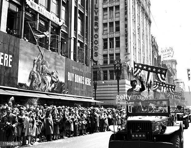 American military commander General George S Patton stands in his parade jeep as he acknowledges the cheers of onlookers who line the streets of Los...