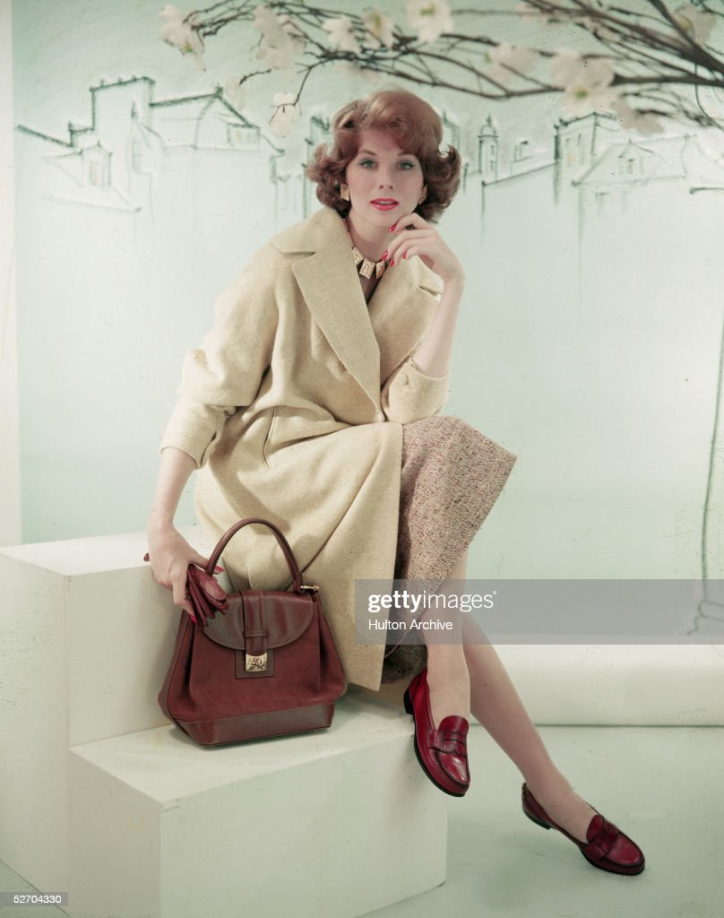 American model and actress Suzy Parker (1932 - 2003) poses as she sits on a step next to a purse, late 1950s.