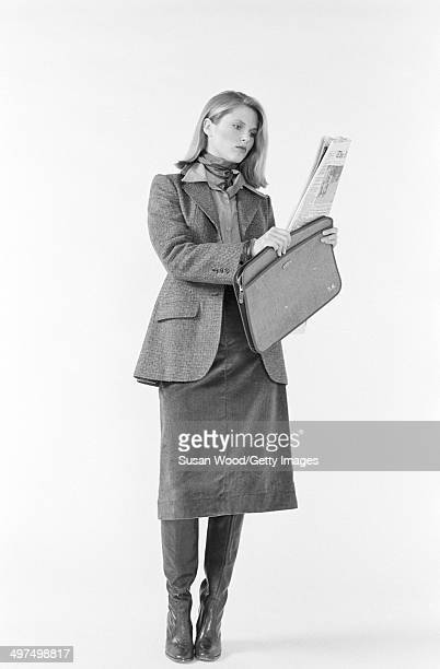 American model Christie Brinkley poses dressed in business attire against a white background 1976 She wears a neckerchief a tweed jacket over a...