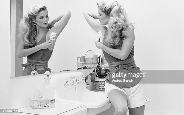 American model Christie Brinkley sits on the edge of a bathroom sink and shaves her armpit with a safty razor 1980