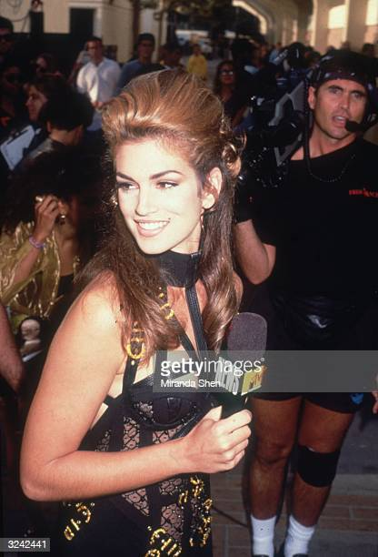 American model Cindy Crawford holds a microphone in front of a cameraman outside the MTV Music Video Awards during her coverage of the event for MTV...