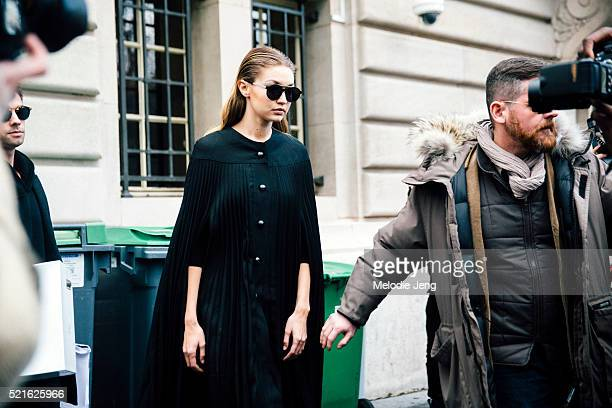 American model Gigi Hadid exits the Giambattista Valli show at Grand Palais in slick combed back hair and a black button and pleated dress/cape on...