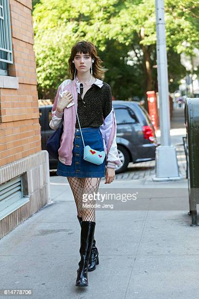 American model Grace Hartzel wears white bluetooth headphones a light pink souvenir jacket off one shoulder a green spotted top with safety pins a...