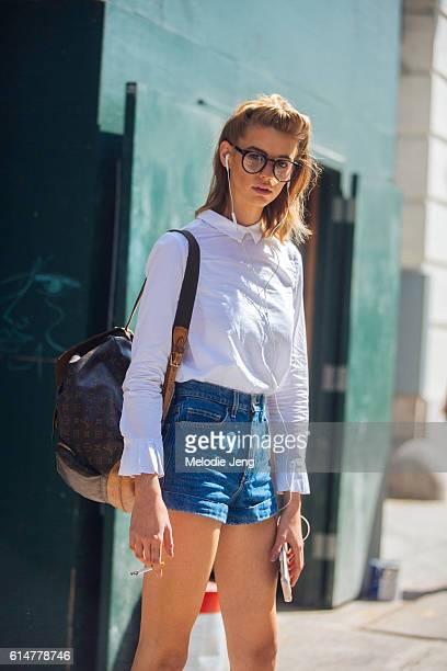 American model Michi Delane wears blackframe glasses a white button up top with a peter pan collar and unique sleeves high waisted denim shorts and...