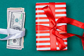 Concept: a gift or money. american money with gift box on a green background