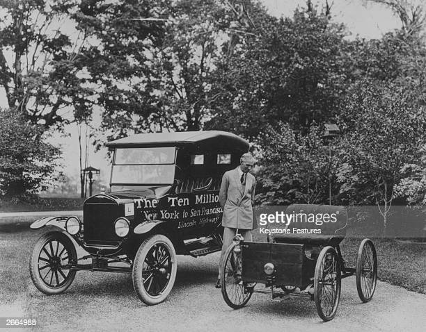 American motor vehicle industry pioneer Henry Ford standing next to the first and the ten millionth ModelT Ford