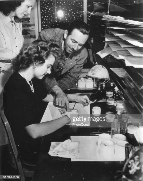 American movie producer artist and animator Walt Disney leans over painter Edith Moore as she works on an animation cel Burbank California 1943