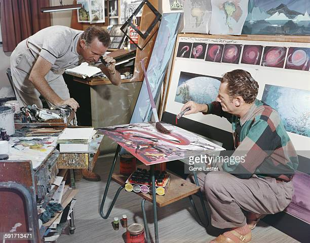 American movie producer artist and animator Walt Disney looks through a lens at an oversized paintbrush while an unidentified man drips paint from a...