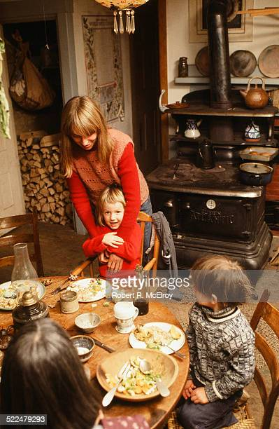 American Mrs Squidge Davis and her children eat at the table in her kitchen with a woodburning stove in the background Monroe Maine January 2 1978