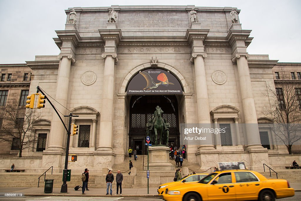 American Museum of Natural History in New York City with yellow taxi.