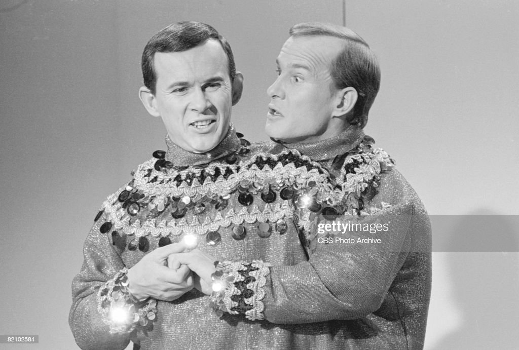 American musician and comedian brothers Dick (left) and Tom Smothers pose together in matching. sparkly sweaters on an episode of their variety show 'The Smothers Brothers Comedy Hour,' December 15, 1967.