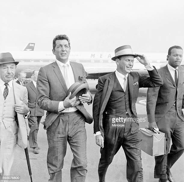 American musician and screen legend Frank Sinatra descends the steps of the plane as he arrives at Heathrow airport with Dean Martin and their friend...