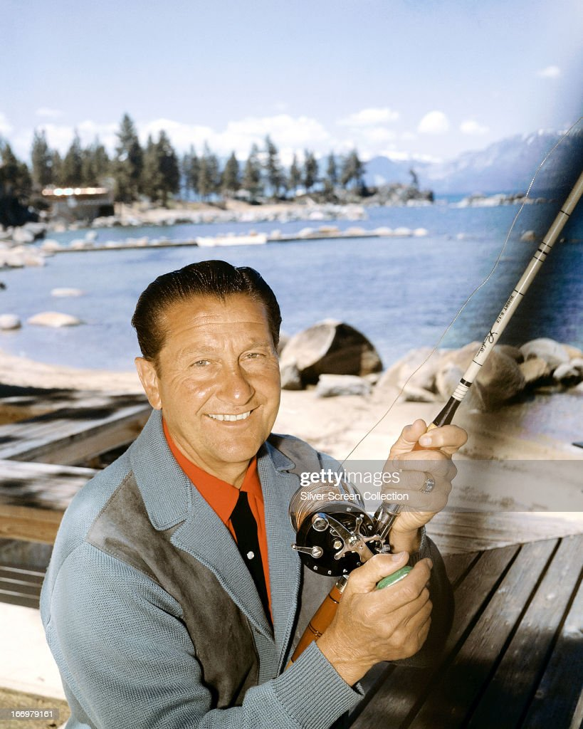 American musician and TV presenter <a gi-track='captionPersonalityLinkClicked' href=/galleries/search?phrase=Lawrence+Welk&family=editorial&specificpeople=714731 ng-click='$event.stopPropagation()'>Lawrence Welk</a> (1903 - 1992) holding a fishing rod in front of a backdrop of a lake, circa 1955.