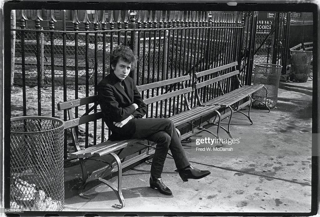American musician <a gi-track='captionPersonalityLinkClicked' href=/galleries/search?phrase=Bob+Dylan&family=editorial&specificpeople=203289 ng-click='$event.stopPropagation()'>Bob Dylan</a> (born Robert Zimmerman) sits on a bench in Sheridan Square Park, New York, New York, January 22, 1965.