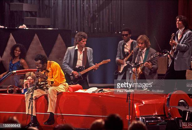 American musician Chuck Berry sits on a convertible as he performs with British musician Keith Richards and American musicians Robert Cray Joe Walsh...