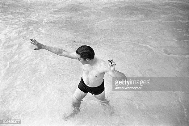 Alfred Wertheimer/Getty Images American musician Elvis Presley stands in the swimming pool of his family's recently purchased home as he holds is...