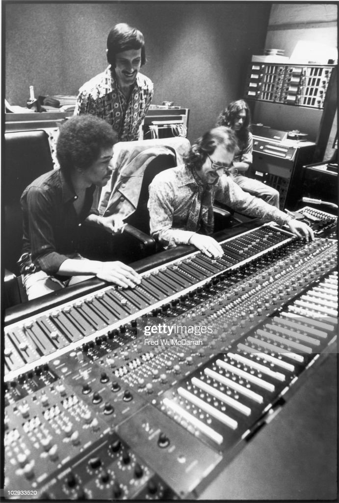 American musician Jimi Hendrix (1942 - 1970) (seated left), South African-born American music producer and engineer Eddie Kramer (seated center) and studio manager Jim Marron (standing) make adjustments to the mixing board in the control room of Hendrix's then still under construction Electric Lady Studio, New York, New York, June 17, 1970.