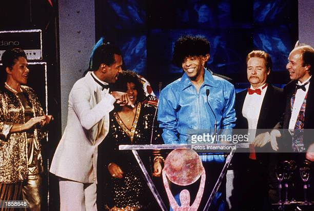 American musician Sly Stone and members of his band The Family Stone stand on stage as they are inducted into the Rock Roll Hall Of Fame in Los...