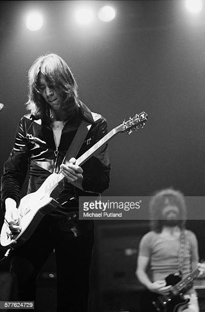 American musician Tom Scholz performing with American rock group Boston 19th April 1977 In the background is singer and guitarist Brad Delp