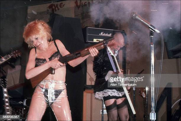American musician Wendy O Williams of the group the Plasmatics fires a shotgun onstage at CBGB New York New York April 19 1979 Richie Stotts plays...