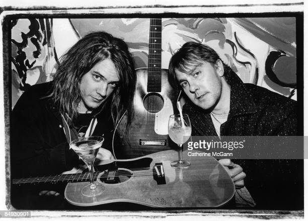 American musicians Dan Murphy and Dave Pirner of the band Soul Asylum pose for a portrait resting their drinks on a guitar in November 1992 in New...