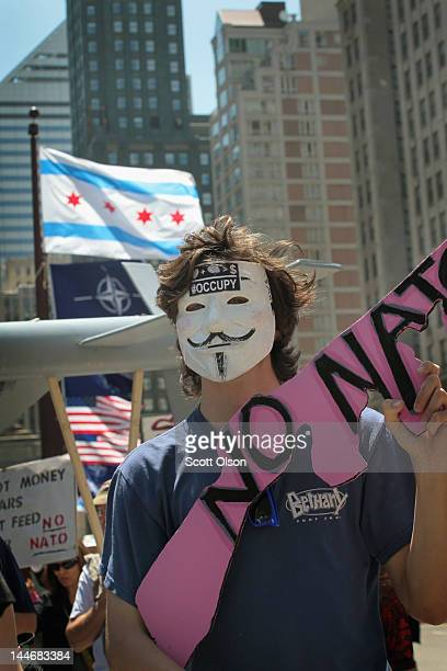 American NATO and Chicago's city flags fly above the Michigan Avenue bridge as antiwar protestors organized by CODEPINK march across May 17 2012 in...