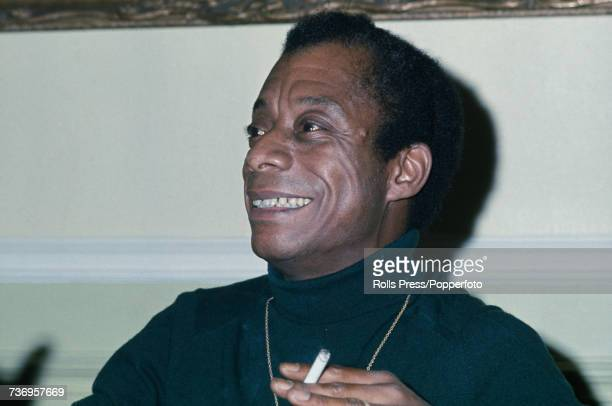 American novelist and playwright James Baldwin pictured smoking a cigarette at a press conference in London on 24th August 1971