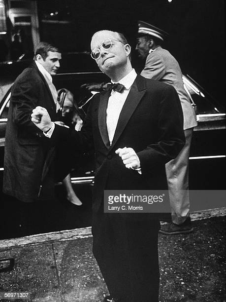 American novelist short story writer and playwright Truman Capote dressed in a tuxedo does a little dance on the street as he arrives for a...