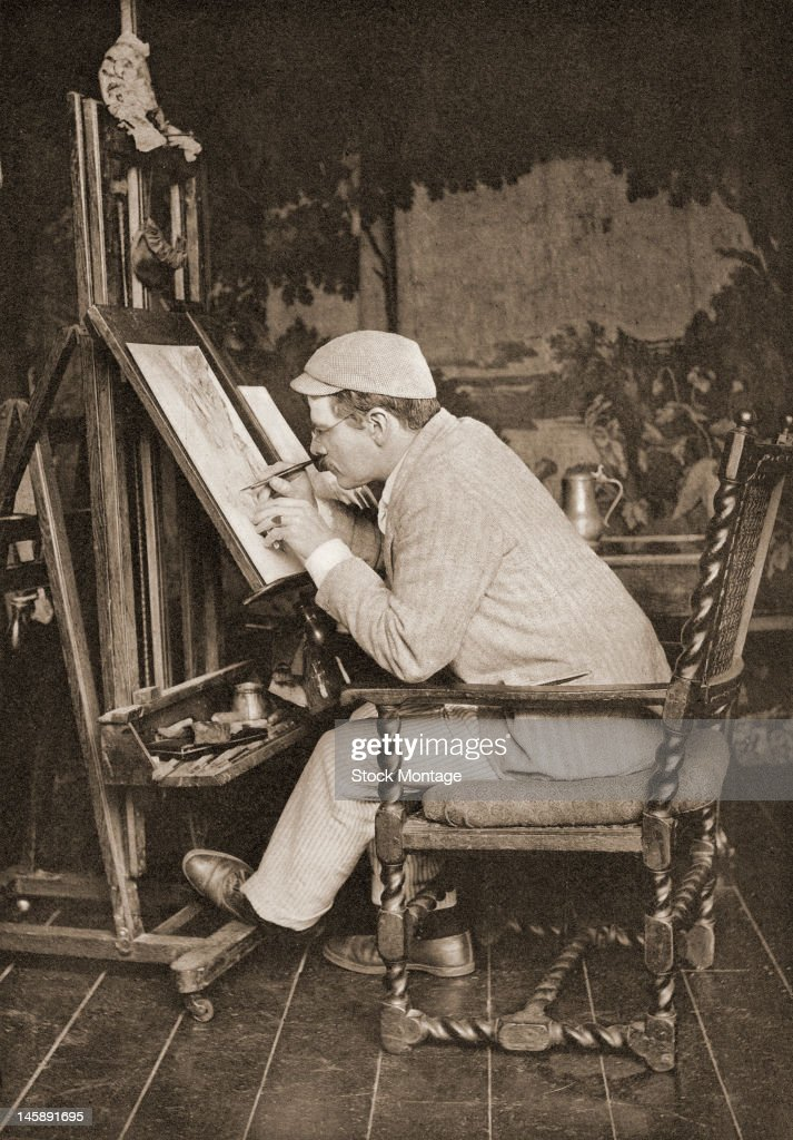 American painter and illustrator Edwin A. Abbey (1852 - 1911) works at an easel in a studio, late 1880s.
