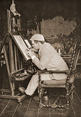 American painter and illustrator Edwin A Abbey works at an easel in a studio late 1880s