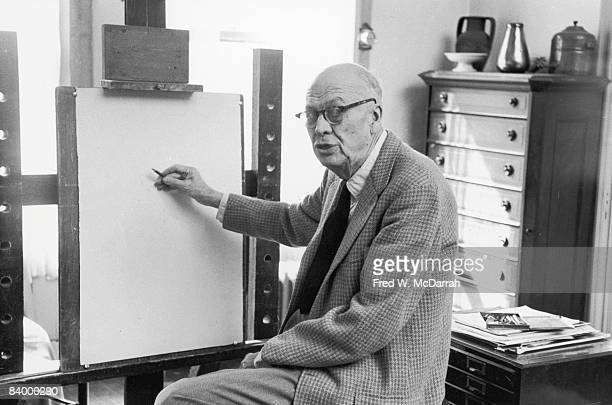 American painter Edward Hopper looks over his shoulder as he holds a pencil up to paper mounted on an easel 1962