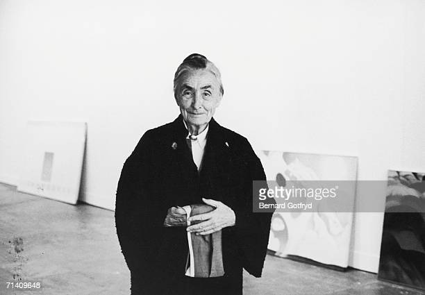 American painter Georgia O'Keefe stands and smiles as she wears a dark overcoat in an art gallery New York 1974