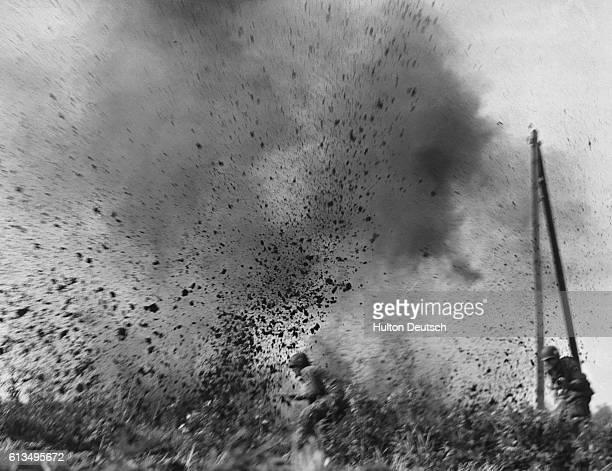 American paratroopers involved in an assault on Arnhem during World War II run through a muddy field under heavy German artillery fire