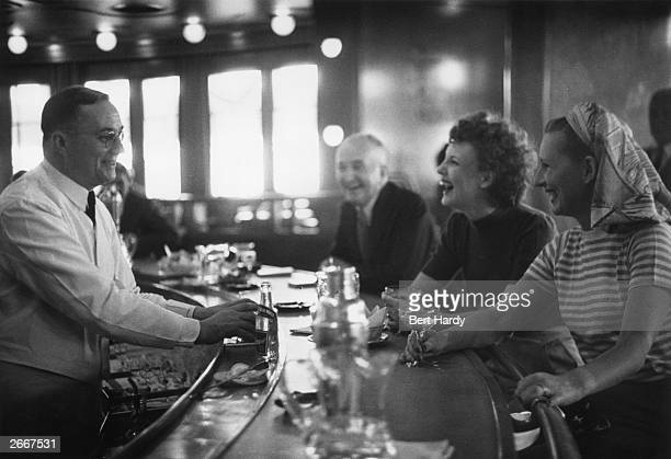 American passengers enjoying drinks in the bar on board the Cunard liner Queen Elizabeth as it makes its way to Britain across the Atlantic Original...