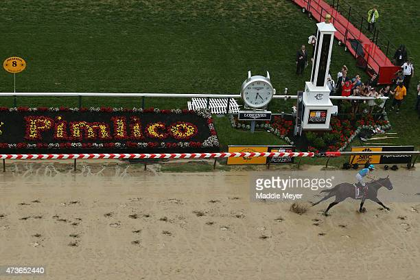 American Pharoah ridden by Victor Espinoza crosses the finish line to win the 140th running of the Preakness Stakes at Pimlico Race Course on May 16...