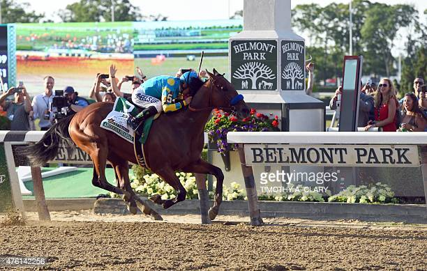 American Pharoah ridden by Victor Espinoza crosses the finish line to win the 147th Belmont Stakes at Belmont Park on June 6 2015 in Elmont New York...