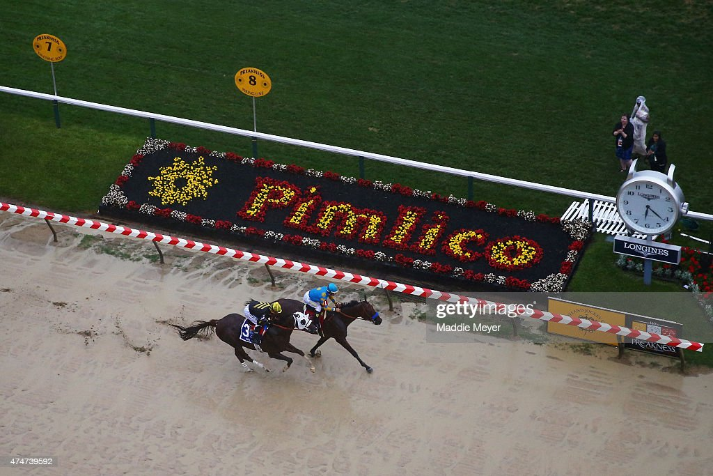 American Pharoah ridden by Victor Espinoza races against Mr Z ridden by Corey S Nakatani heading into the first turn during the 140th running of the...