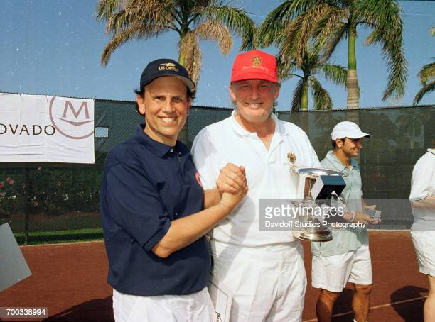 American philanthropist and former financier Michael Milken and real estate developer Donald Trump as they pose together at the CapCure ProAm...