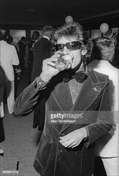 American photographer and artist Robert Mapplethorpe drinks from a glass at the Man Ray Bal Blanc at the New York Cultural Center New York New York...