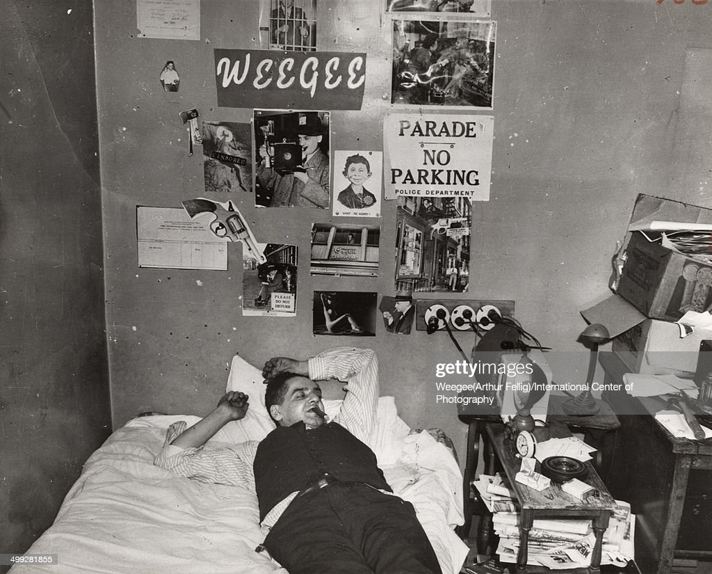 American photographer Arthur Fellig, better known as <a gi-track='captionPersonalityLinkClicked' href=/galleries/search?phrase=Weegee&family=editorial&specificpeople=207086 ng-click='$event.stopPropagation()'>Weegee</a> (1899 - 1968) lies on his bed, eyes clsoed and a cigar in his mouth, in a photograph entitled 'My headquarters,' New York, New York, late 1930s. (Photo by <a gi-track='captionPersonalityLinkClicked' href=/galleries/search?phrase=Weegee&family=editorial&specificpeople=207086 ng-click='$event.stopPropagation()'>Weegee</a> (Arthur Fellig)/International Center of Photography/Getty Images)
