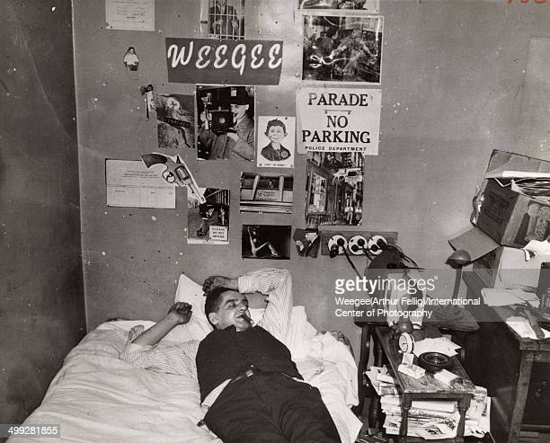 American photographer Arthur Fellig better known as Weegee lies on his bed eyes clsoed and a cigar in his mouth in a photograph entitled 'My...