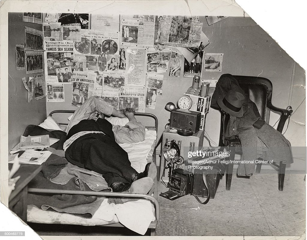American photographer Arthur Fellig, better known as <a gi-track='captionPersonalityLinkClicked' href=/galleries/search?phrase=Weegee&family=editorial&specificpeople=207086 ng-click='$event.stopPropagation()'>Weegee</a> (1899 - 1968) lies on his bed, an arm over his eyes and a cigar in his mouth, in a photograph entitled 'My Studio,' New York, New York, mid 1930s. (Photo by <a gi-track='captionPersonalityLinkClicked' href=/galleries/search?phrase=Weegee&family=editorial&specificpeople=207086 ng-click='$event.stopPropagation()'>Weegee</a>(Arthur Fellig)/International Center of Photography/Getty Images)