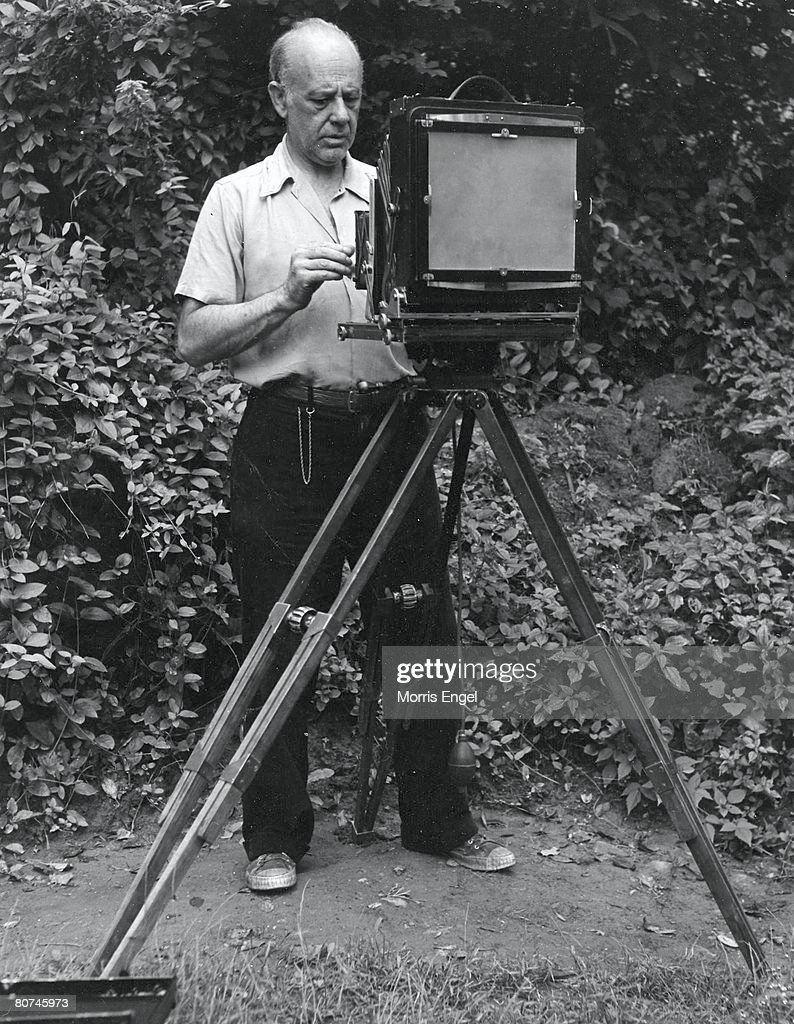 American photographer Paul Strand (1890 - 1976) adjusts the lens of his camera equipment, New Jersey, 1947.