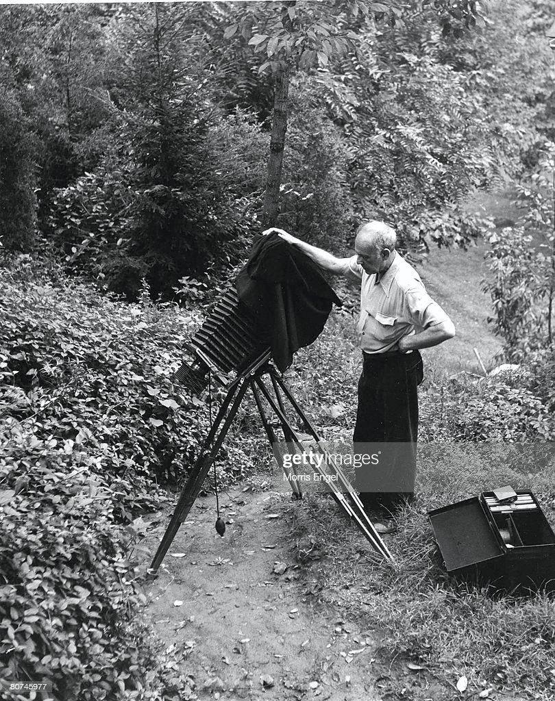 American photographer Paul Strand (1890 - 1976) sets up his camera equipment on a dirt path, New Jersey, 1947.