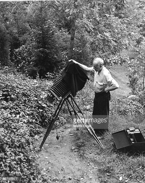 American photographer Paul Strand sets up his camera equipment on a dirt path New Jersey 1947