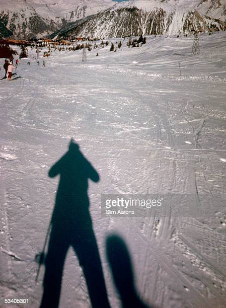 American photographer Slim Aarons takes a picture of his own shadow on the ski slopes at Courcheval France 1963