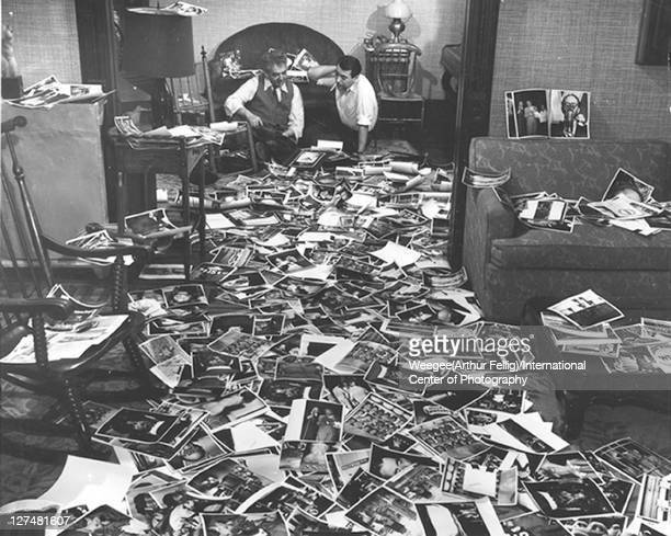 American photographer Weegee and collaborator Mel Harris sit on the floor and look through dozens of the former's photos strewn across the floor...