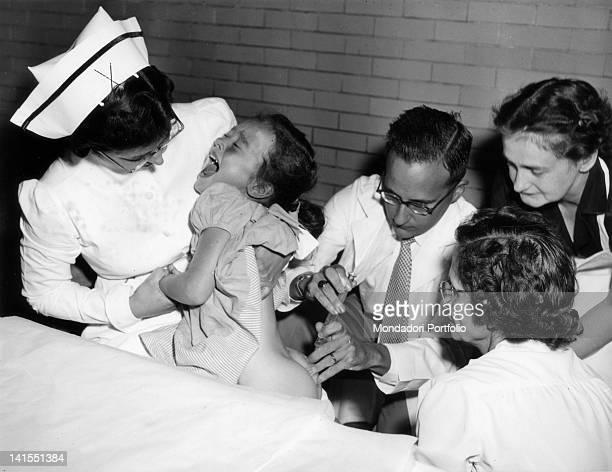 American physician Jonas Salk developer of the polio vaccine inoculating the vaccine to a girl USA 1950s