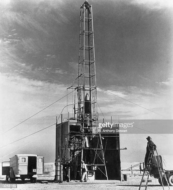 American physicist Dr Robert H Goddard stands and leans back on a step ladder as he oversees launch preparations of a rocket in a tower Roswell New...