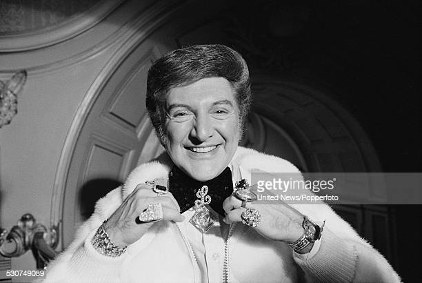 American pianist and entertainer Liberace pictured wearing a zip up fur jacket and ornate jewellery in London on 28th November 1977